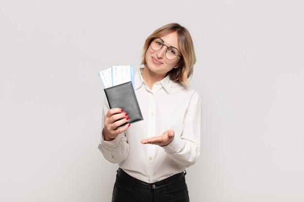 Jonge blonde vrouw die vrolijk glimlacht, zich gelukkig voelt en een concept in exemplaarruimte met handpalm toont