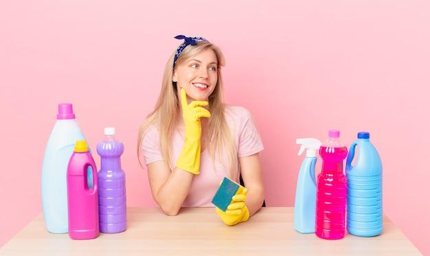 Jonge blonde vrouw die vrolijk lacht en dagdroomt of twijfelt. huishoudster concept