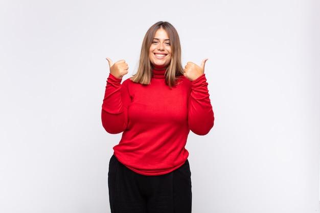 Jonge blonde vrouw die vrolijk lacht en er gelukkig uitziet, zich zorgeloos en positief voelt met beide duimen omhoog