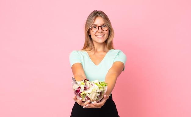 Jonge blonde vrouw die vrolijk lacht met vriendelijk en een concept aanbiedt en toont en een salade vasthoudt
