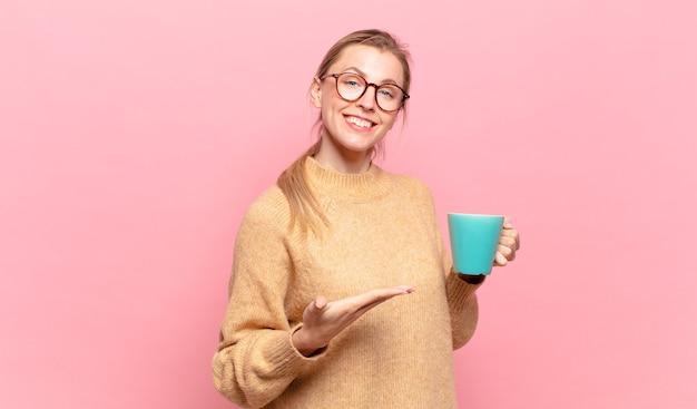 Jonge blonde vrouw die vrolijk lacht, zich gelukkig voelt en een concept in kopieerruimte toont met de palm van de hand. koffie concept