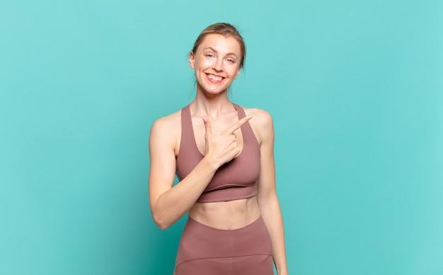 Jonge blonde vrouw die vrolijk lacht, zich gelukkig voelt en naar de zijkant en naar boven wijst, een object in de kopieerruimte laat zien. sport concept