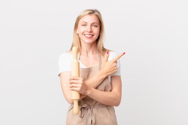Jonge blonde vrouw die vrolijk lacht, zich gelukkig voelt en naar de zijkant wijst. bakker concept