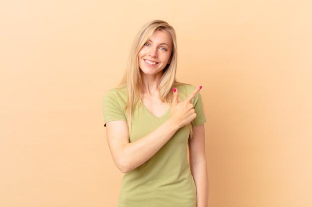 Jonge blonde vrouw die vrolijk lacht, zich gelukkig voelt en naar de zijkant wijst