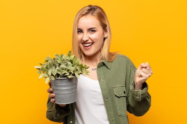 Jonge blonde vrouw die zich blij, verrast en trots voelt, schreeuwt en succes viert met een grote glimlach