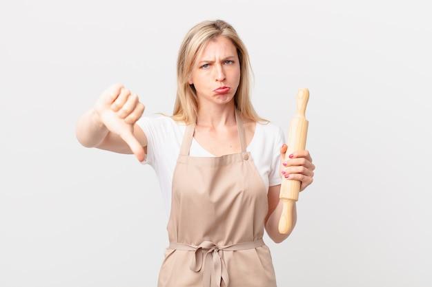 Jonge blonde vrouw die zich boos voelt en duimen naar beneden laat zien. bakker concept