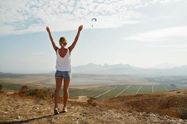 Jonge blonde vrouw die zich bovenop heuvel bevindt