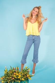 Jonge blonde vrouw die zich dichtbij mand met tulpen op blauwe achtergrond bevindt