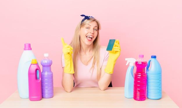 Jonge blonde vrouw die zich een gelukkig en opgewonden genie voelt na het realiseren van een idee. huishoudster concept