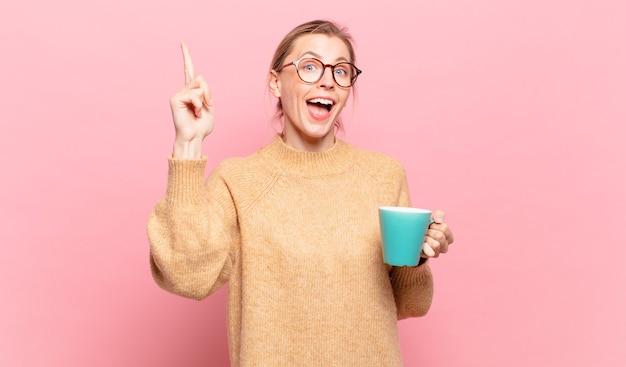 Jonge blonde vrouw die zich een gelukkig en opgewonden genie voelt na het realiseren van een idee, vrolijk vinger opstekend, eureka!. koffie concept