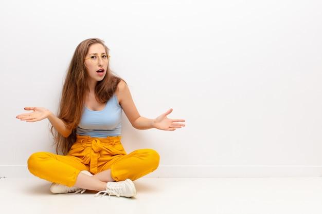 Jonge blonde vrouw die zich geen idee en verward voelt, geen idee heeft, absoluut verbaasd is over een domme of dwaze blik zittend op de vloer