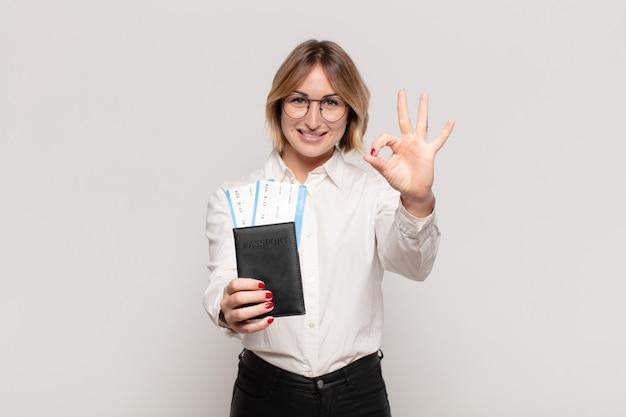 Jonge blonde vrouw die zich gelukkig, ontspannen en tevreden voelt, goedkeuring toont met een goed gebaar, glimlachend