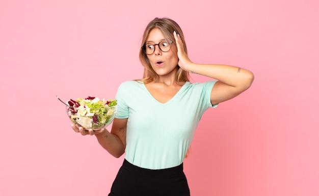 Jonge blonde vrouw die zich gelukkig, opgewonden en verrast voelt en een salade vasthoudt