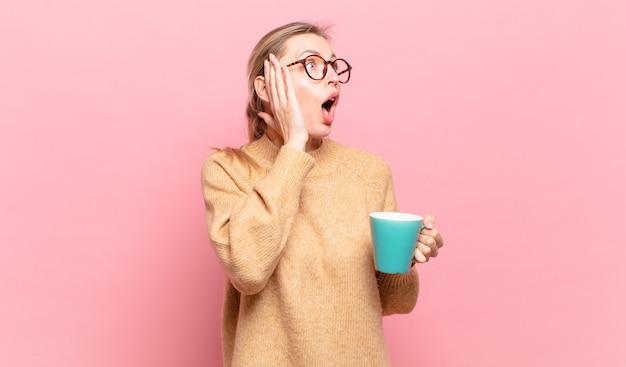 Jonge blonde vrouw die zich gelukkig, opgewonden en verrast voelt, opzij kijkend met beide handen op het gezicht. koffie concept