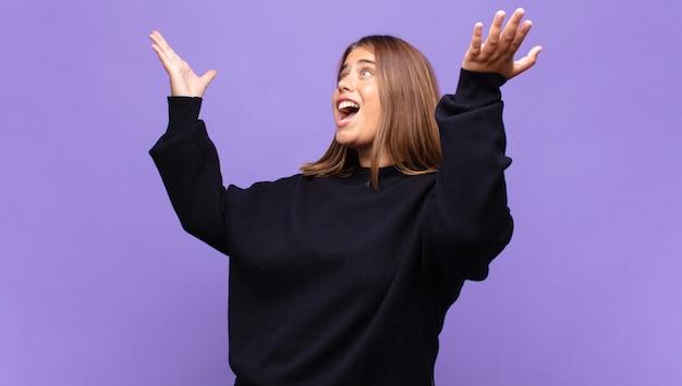 Jonge blonde vrouw die zich gelukkig, verbaasd, gelukkig en verrast voelt en de overwinning viert met beide handen in de lucht