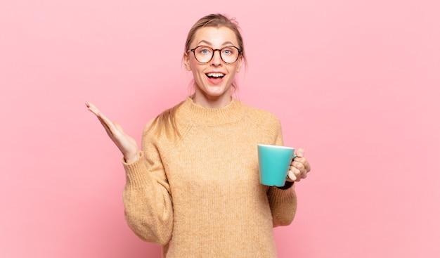 Jonge blonde vrouw die zich gelukkig, verrast en opgewekt voelt, met een positieve houding glimlacht, een oplossing of idee realiseert