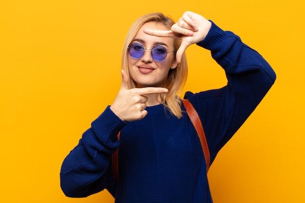 Jonge blonde vrouw die zich gelukkig, vriendelijk en positief voelt, lacht en een portret of fotolijst met handen maakt