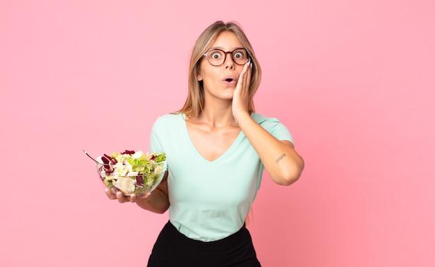 Jonge blonde vrouw die zich geschokt en bang voelt en een salade vasthoudt