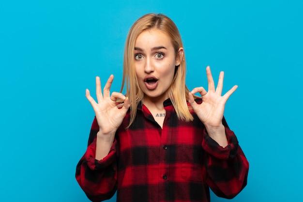 Jonge blonde vrouw die zich geschokt, verbaasd en verrast voelt, goedkeuring toont en met beide handen een goed teken maakt