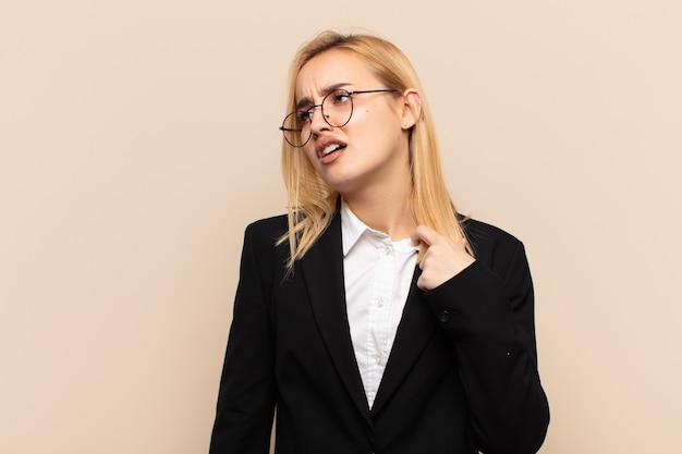 Jonge blonde vrouw die zich gestrest, angstig, moe en gefrustreerd voelt en de hals van het shirt trekt