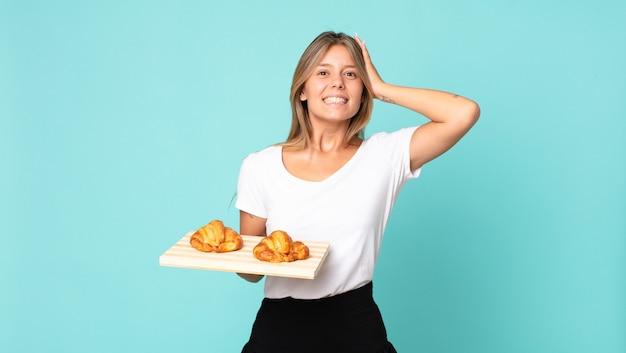 Jonge blonde vrouw die zich gestrest, angstig of bang voelt, met de handen op het hoofd en een croissantblad vasthoudt