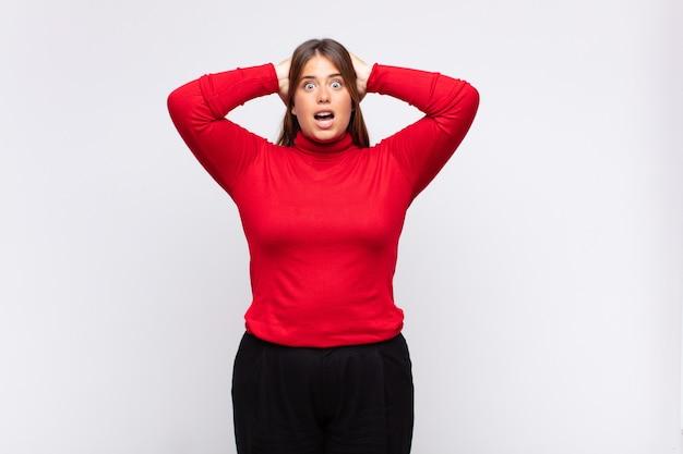 Jonge blonde vrouw die zich gestrest, bezorgd, angstig of bang voelt, met de handen op het hoofd, in paniek bij vergissing