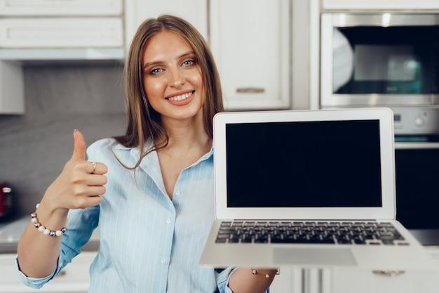 Jonge blonde vrouw die zich in kithen bevindt en leeg scherm laptopcomputer toont