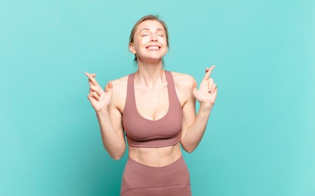 Jonge blonde vrouw die zich nerveus en hoopvol voelt, vingers kruist, bidt en hoopt op geluk. sport concept