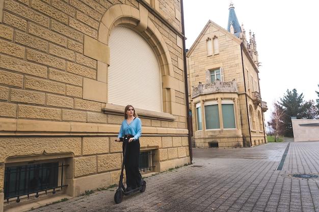 Jonge blonde vrouw die zich op een e-scooter in de stad beweegt.