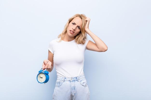 Jonge blonde vrouw die zich verbaasd en verward voelt, haar hoofd krabt en naar de kant kijkt met een klok vast