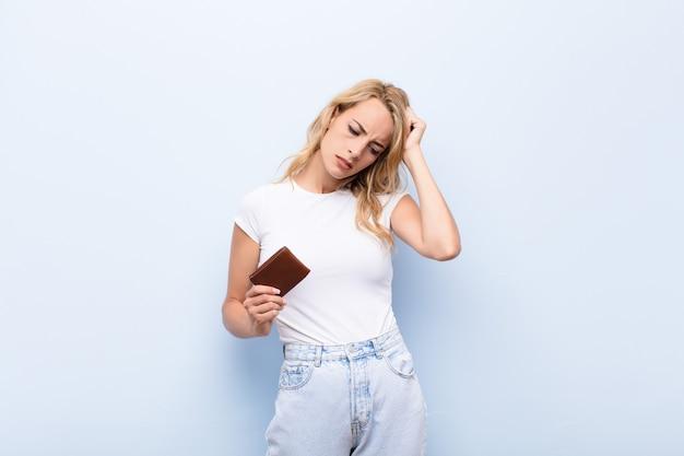 Jonge blonde vrouw die zich verbaasd en verward voelt, haar hoofd krabt en naar de kant kijkt met een portemonnee vast