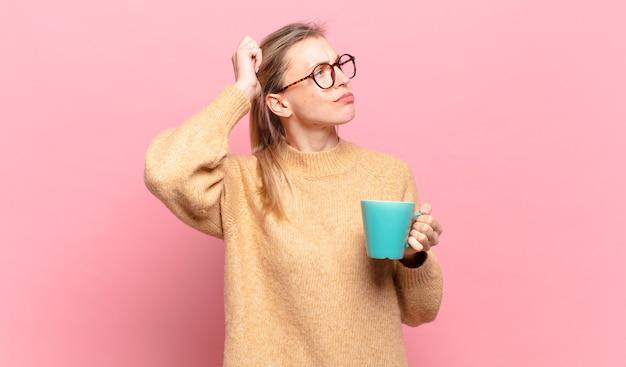 Jonge blonde vrouw die zich verbaasd en verward voelt, haar hoofd krabt en opzij kijkt. koffie concept