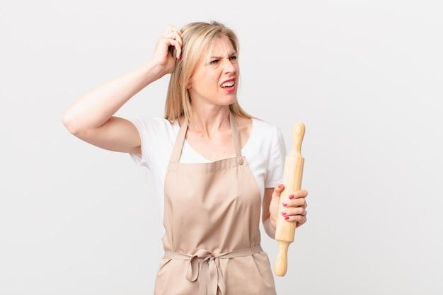 Jonge blonde vrouw die zich verbaasd en verward voelt, hoofd krabben. bakker concept