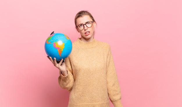 Jonge blonde vrouw die zich verbaasd en verward voelt, met een stomme, verbijsterde uitdrukking op zoek naar iets onverwachts. wereld concept