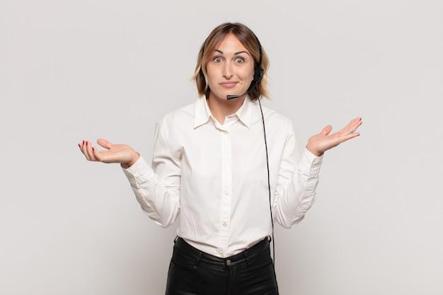 Jonge blonde vrouw die zich verbaasd en verward voelt, twijfelt, weegt of verschillende opties kiest met grappige uitdrukking