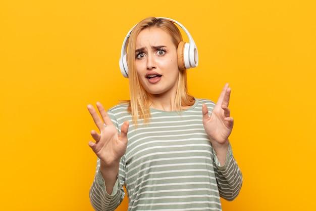 Jonge blonde vrouw die zich verdoofd en bang voelt, bang voor iets angstaanjagends, met de handen vooraan open en zegt blijf weg