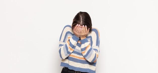 Jonge blonde vrouw die zich verdrietig, gefrustreerd, nerveus en depressief voelt, gezicht bedekt met beide handen, huilend