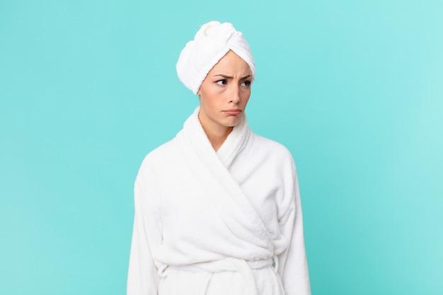 Jonge blonde vrouw die zich verdrietig, overstuur of boos voelt en opzij kijkt. doucheconcept.