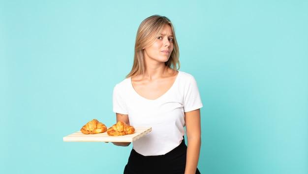 Jonge blonde vrouw die zich verdrietig, overstuur of boos voelt en opzij kijkt en een croissantblad vasthoudt