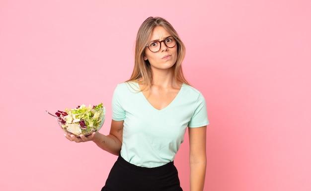 Jonge blonde vrouw die zich verdrietig, overstuur of boos voelt en opzij kijkt en een salade vasthoudt