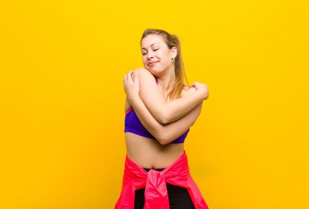 Jonge blonde vrouw die zich verliefd voelt, lacht, zichzelf knuffelt en knuffelt, vrijgezel blijft, egoïstisch en egocentrisch is. sport concept