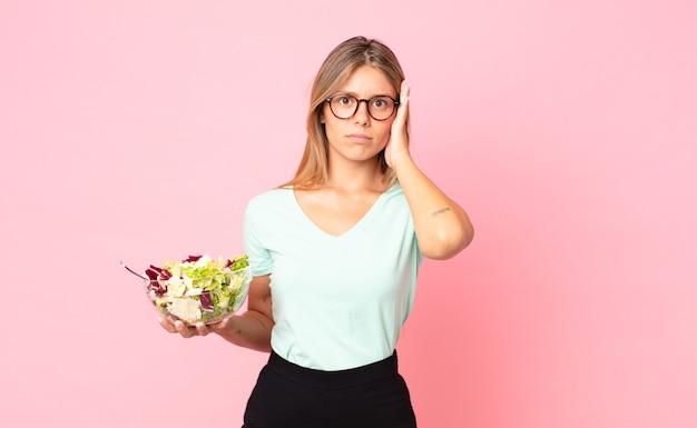 Jonge blonde vrouw die zich verveeld, gefrustreerd en slaperig voelt na een vermoeiende maaltijd en een salade vasthoudt
