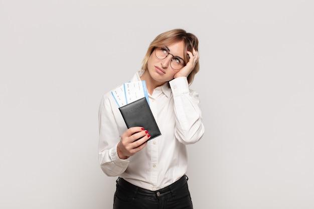 Jonge blonde vrouw die zich verveeld, gefrustreerd en slaperig voelt na een vermoeiende, saaie en vervelende taak, gezicht met hand vasthoudend