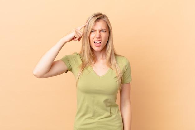 Jonge blonde vrouw die zich verward en verbaasd voelt en laat zien dat je gek bent