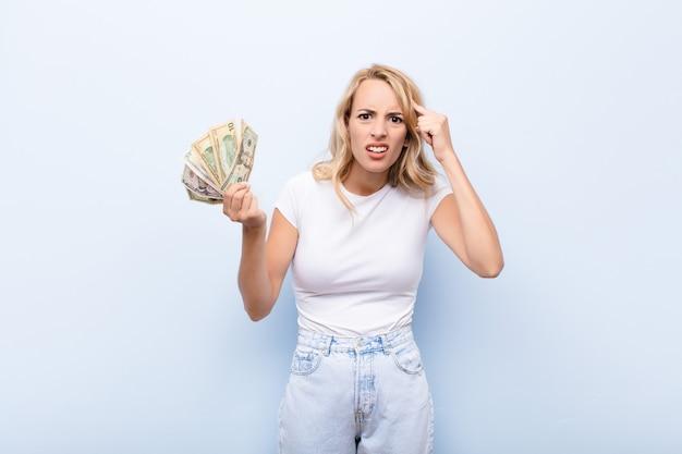 Jonge blonde vrouw die zich verward en verbaasd voelt en laat zien dat je gek, gek of gek bent met dollarbiljetten