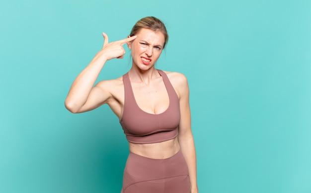 Jonge blonde vrouw die zich verward en verbaasd voelt en laat zien dat je gek, gek of gek bent. sport concept