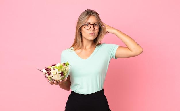 Jonge blonde vrouw die zich verward en verbaasd voelt, laat zien dat je gek bent en een salade vasthoudt