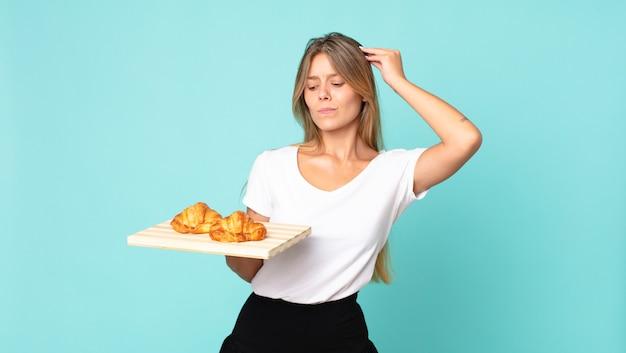 Jonge blonde vrouw die zich verward en verward voelt, haar hoofd krabt en een croissantblad vasthoudt