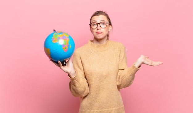 Jonge blonde vrouw die zich verward en verward voelt, twijfelt, weegt of verschillende opties kiest met grappige uitdrukking