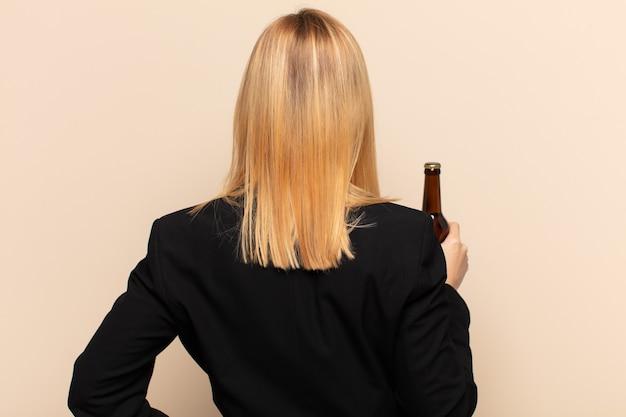 Jonge blonde vrouw die zich verward of vol voelt of twijfels en vragen, zich afvraagt, met de handen op de heupen, zicht naar achteren